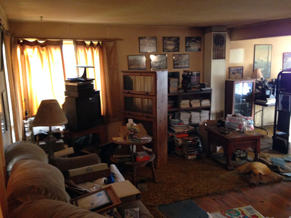 A lounge room full of clutter with old furniture and possessions